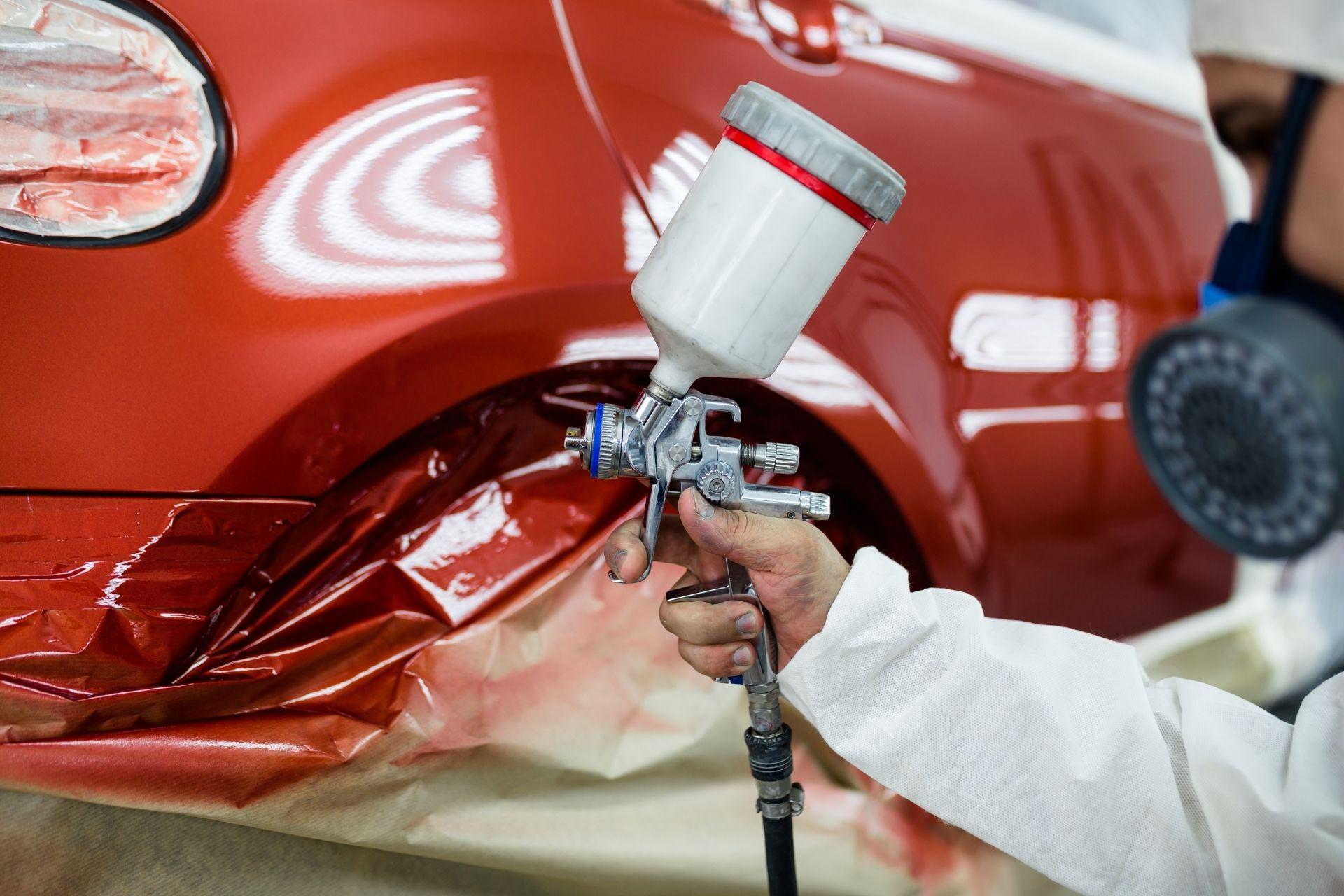 guy spraying car in red
