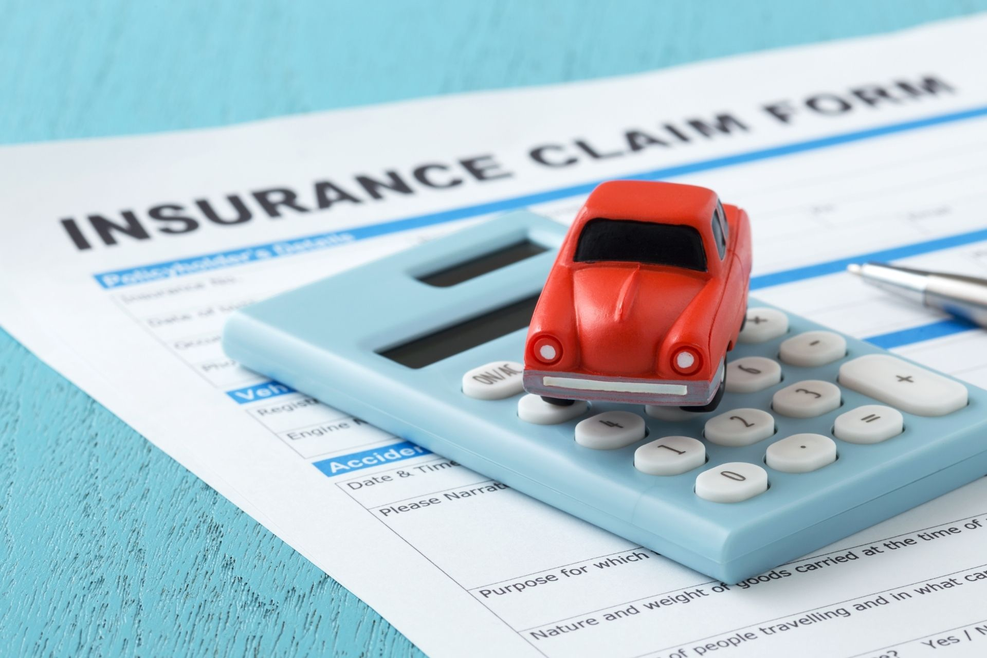 red car and calculator on insurance form