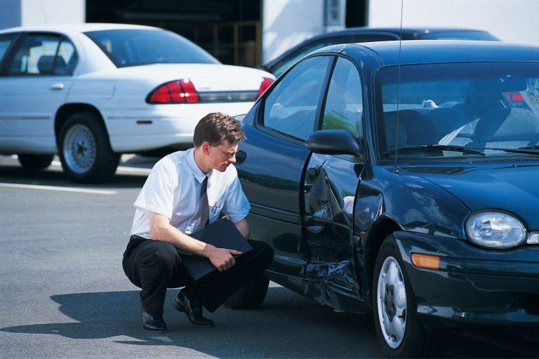 guy wearing white t shirt checking on car dent