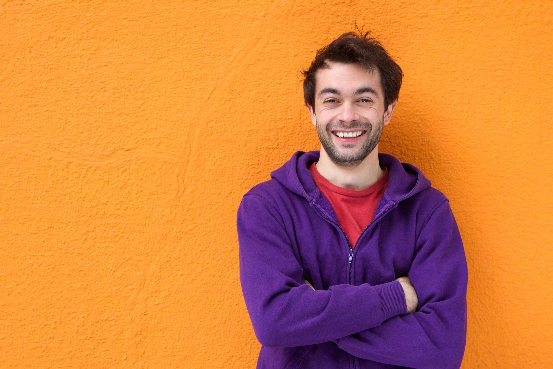 guy smiling wear purple hoodie-orange background