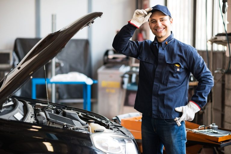 smiling technician in car workshop
