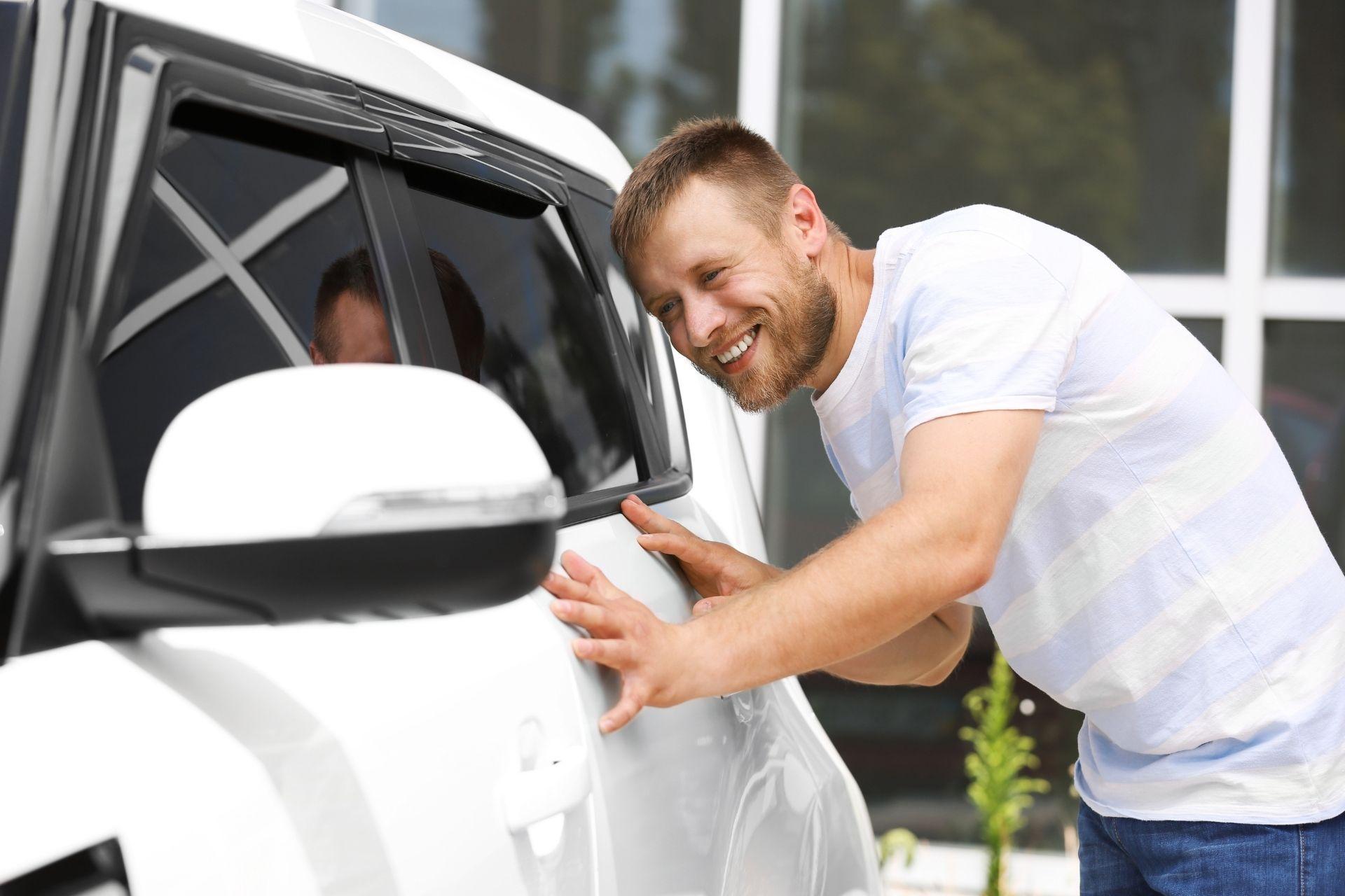 guy wearing white checking on car smiling